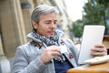 Mature man sitting in outdoor cafe websurfing on tablet Royalty Free Stock Photo