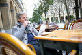 Mature man sitting in outdoor coffee shop Royalty Free Stock Photo