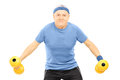 Mature man in sportswear exercising with dumbbells Stock Photography