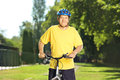 Mature man in sportswear posing on his bike in a park bicycle Stock Photo