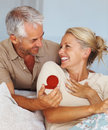 Mature man surprising his wife with a gift Royalty Free Stock Photography