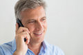 Mature man talking on cellphone closeup of happy businessman listens the phone Royalty Free Stock Photography