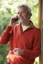 Mature Man Using Cordless Phone At Home Royalty Free Stock Photo