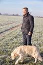 Mature man walking dog in frosty landscape Royalty Free Stock Image