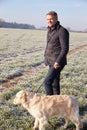 Mature man walking dog in frosty landscape Stock Photo