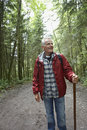 Mature man walking on forest path smiling in the Stock Images