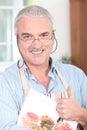 Mature man wearing apron Stock Images