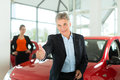 Mature man with woman and auto in car dealership Stock Photo