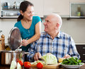 Mature married couple cooking lunch together in domestic kitchen Stock Photo
