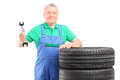 Mature mechanic standing with car tires and holding a wrench Stock Photo