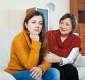 Mature mother asks for forgiveness from adult daughter after qua quarrel at home focus on girl Royalty Free Stock Image