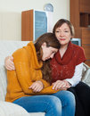 Mature mother comforting crying adult daughter at home Stock Image