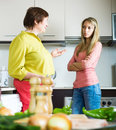 Mature mother with daughter having serious conversation adult in kitchen Royalty Free Stock Image