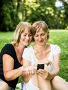 Mature mother and daughter with smartphone Royalty Free Stock Photography