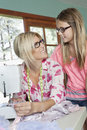 Mature mother looking at daughter while sewing cloth Royalty Free Stock Photography