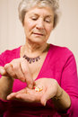 Mature older woman taking a tablet or pill Royalty Free Stock Photos