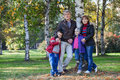 Mature parents with children stand together in park full length standing Royalty Free Stock Image