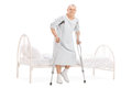 Mature patient with crutches getting out of bed full length portrait a isolated on white background Royalty Free Stock Images