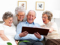 Mature people looking at photo album Royalty Free Stock Image