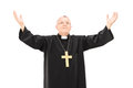 Mature priest with his hands in the air isolated on white background Stock Image