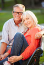 Mature romantic couple sitting on park bench together Stock Image