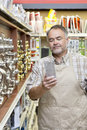 Mature salesperson reading instructions in hardware store Stock Photography