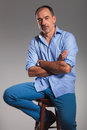 Mature seated casual man in jeans with arms crossed Royalty Free Stock Photo