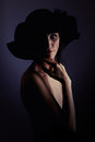 Mature sensuality woman with bared shoulders shirtless in black hat in dark Stock Photo