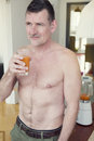 Mature shirtless man drinking glass of juice standing in living room and Royalty Free Stock Photography