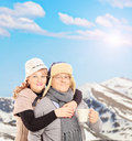 Mature smiling couple holding a cup and posing outside in snowy landscape shot with tilt shift Stock Photography