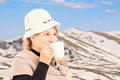Mature smiling woman drinking a hot tea and posing outside with snowy mountain in the background Stock Photography