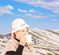 Mature smiling woman drinking a tea and posing outside in snowy hot landscape shot with tilt shift lens Stock Photography