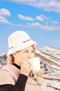 Mature smiling woman drinking a tea with snowy mountain in the hot and posing background Royalty Free Stock Image