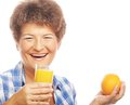 Mature smiling woman with orange juice isolated on white Royalty Free Stock Photos