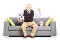 Mature sport fan holding a soccer ball and watching sport isolated on white background Royalty Free Stock Photo