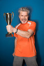 Mature sportsman holding trophy cup on blue