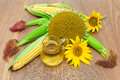 Mature sunflowers, corn and oil in a glass jar close-up on woode Royalty Free Stock Photo