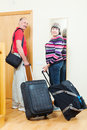 Mature tourists with luggage near door two in home Royalty Free Stock Image