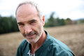 Mature unshaven farmer standing in field portrait of cheerful agricultural Royalty Free Stock Photography