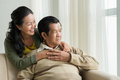 Mature vietnamese couple at home happy embracing looking through the window Royalty Free Stock Photo