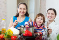 Mature woman and adult daughter with girl cook lunch Stock Image