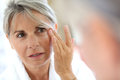Mature woman applying cream on face senior anti wrinkles Royalty Free Stock Image