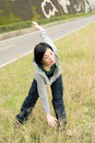 Mature woman of asian stretch her body in outdoor park Stock Photography