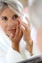 Mature woman in bathrobe taking care of skin senior applying anti wrinkles cream Royalty Free Stock Photo