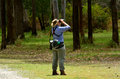 Mature woman birdwatching watching through binoculars in coombabah lake conservation park in gold coast australia Royalty Free Stock Photo
