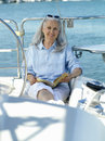 Mature woman on boat with book smiling portrait Royalty Free Stock Photography