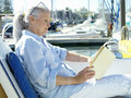 Mature woman on boat reading book side view Stock Image