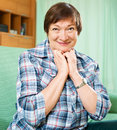 MAture woman in casual clothes sitting on couch Royalty Free Stock Photo