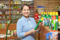 Mature  woman chooses fertilizers at store Stock Photography