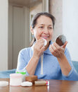 Mature woman cleans the make up from face at home Royalty Free Stock Images